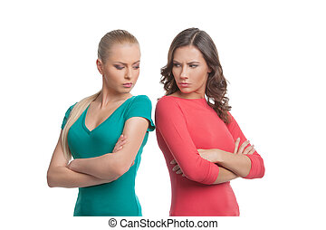 Two angry women. Two angry women looking at each other over...