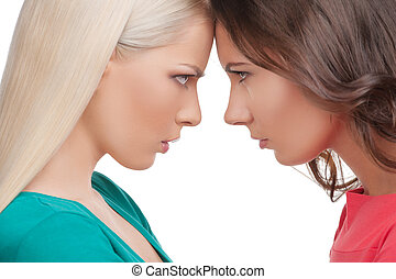 Confrontation. Two angry women standing face to face with...