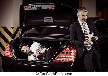 Kidnapped man. Tied up businessman lying in the car trunk...