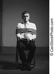 Kidnapped businessman. Black and white image of tied up...