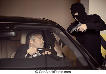 Where is the money? Men in black balaclava holding gun and...