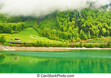 Beautiful emerald mountain lake in Switzerland under low...