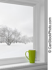 Green cup on a windowsill, with winter landscape seen...