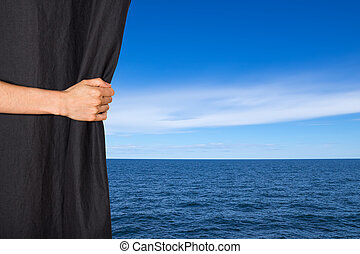 Hand opening black curtain with sea and sky behind it