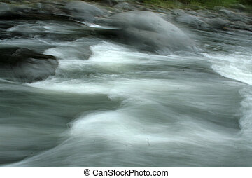 Rushing Water - Rushing water flowing over rocks in a river...