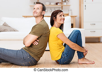 Young couple relaxing on the floor at home sitting barefoot...