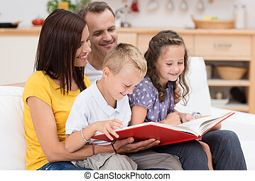Happy family reading a book together with attractive young...