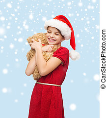 smiling girl in santa helper hat with teddy bear -...