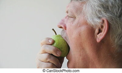 man tries to eat unripe pear - older man bites into pear...
