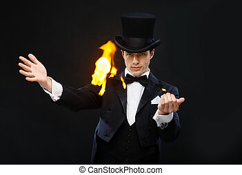 magician in top hat showing trick with fire - magic,...