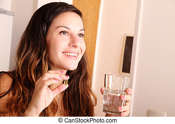 Taking a Pill - A young woman taking a pill with a glass of...