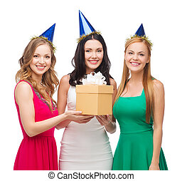 three smiling women in blue hats with gift box -...