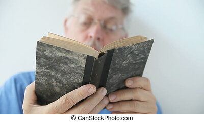 man looking through a book