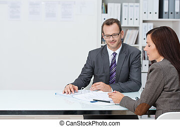 Business man and woman in a meeting in the office sitting at...