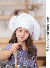 Cute little girl in a white chefs toque standing in the...