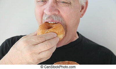 man eats yeast doughnut - older man bites into a fresh...