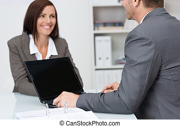 Businessman using a laptop computer in a meeting with a...