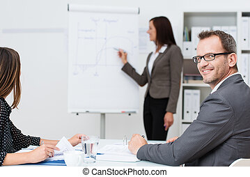 Smiling businessman in a meeting or lecture at the office...