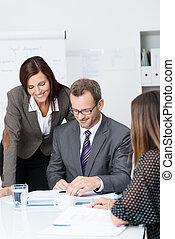 Team of businesspeople in a meeting with focus to a smiling...