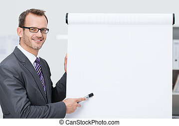 Smiling businessman pointing to a blank flipchart - Smiling...
