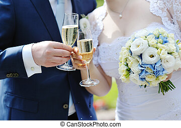 Bride and groom making a toast with champagne glasses after...
