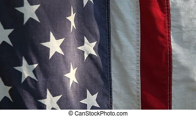 American flag closeup - a very old flag on a sunny morning