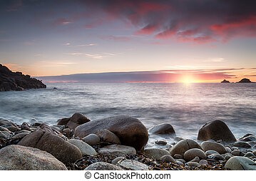 Sunset at Porth Nanven Cove in cornwall - The sun sets over...