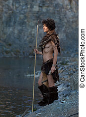 cavewoman fishing near a lake