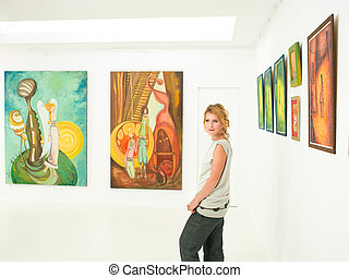young woman visiting art exhibition - young caucasian woman...