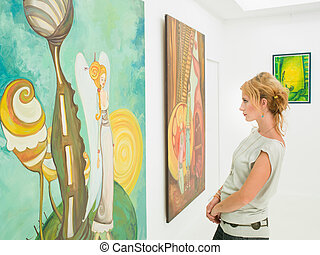 woman contemplating paintings in art gallery - side view of...