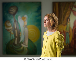 woman visiting art gallery - side view of beautiful...