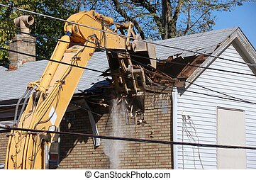 house demolition - old house being demolished by a large...