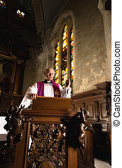 Preaching on a pulpit - Roman catholic priest preaching on...