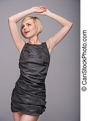 Beautiful fashion model. Beautiful young woman in dress posing and smiling while standing isolated on grey