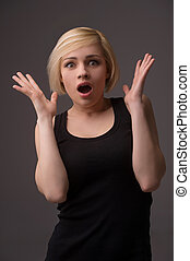 Shocked woman. Surprised young woman gesturing while isolated on grey