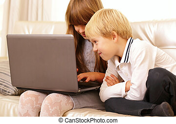 children playing with laptop computer at home