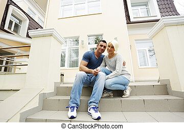 Happy couple sitting on the stairs in front of their house