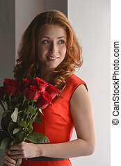 I love roses - Portrait of attractive young woman holding a...