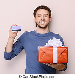 Portrait of young man holding gift box and a credit card....