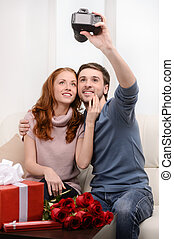 Loving couple taking photograph of themselves. Attractive...