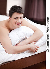 Waking up Handsome young man lying on bed and smiling at...