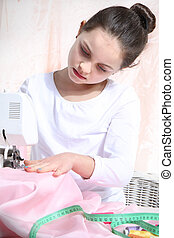 Portrait of little seamstress - little girl sewing on a...