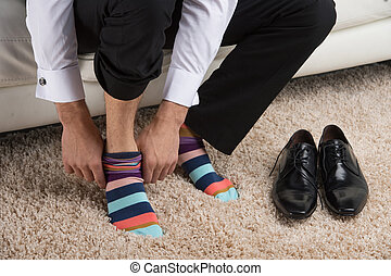 Close up of a man wearing colorful sock under classical...