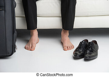 Close up of bare feet of a business man. Having traveling suitcase and shoes near