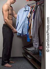Fit male model is choosing a shirt. Staying with nude torso
