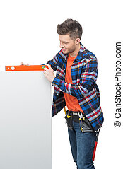 Handyman measuring level. Young confident crafts person measuring the level with special tool
