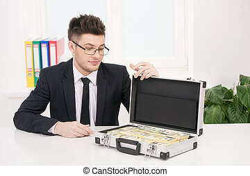Wealthy businessman. Handsome young businessmen in glasses looking at the suitcase full of money