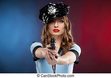 Sexy policewoman. Beautiful young policewoman aiming you with a gun while isolated on colored background