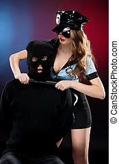 Sexy policewoman at work. Beautiful young policewoman in uniform standing close to the man in black balaclava while isolated on colored background