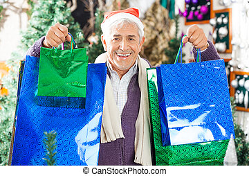 Man Carrying Shopping Bags In Christmas Store - Portrait of...